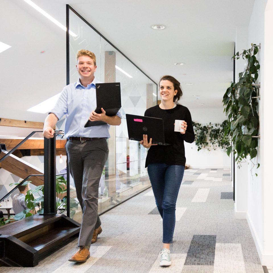 two colleagues at vivid economics striding down hallway carrying laptops