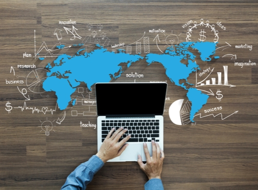 a laptop superimposed over an illustrated blue world map