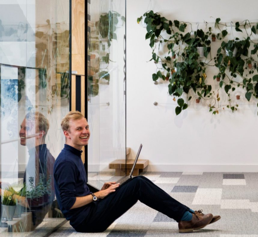 smiling man on laptop sat on floor outside of internal office